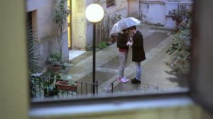 stock-footage-two-lovers-holding-hands-and-kissing-under-umbrella-in-the-rain